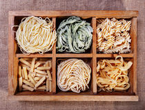 Assorted pasta in wooden box catalog on dark fabric background - Royalty Free Stock Image