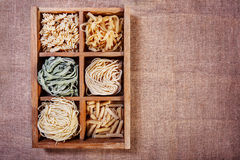 Assorted pasta in wooden box catalog on dark fabric background Royalty Free Stock Photography