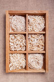Assorted pasta in wooden box catalog on dark fabric background Royalty Free Stock Image