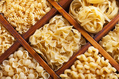 Assorted pasta in wooden compartments. Italian food variety Stock Images