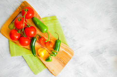 Assorted pepper and tomatoes on wooden background Royalty Free Stock Photography