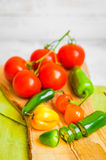 Assorted pepper and tomatoes on wooden background Stock Photography