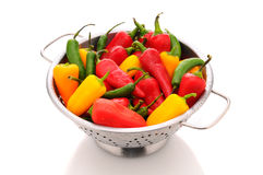 Assorted peppers in colander Stock Photo