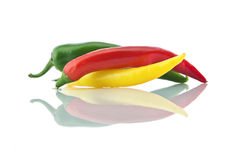 Assorted peppers. Peppers yellow, green and red colors and it's reflection on a white   background Royalty Free Stock Photos