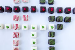 Assorted Petit Fours on White Background. Assorted chocolate petit fours arranged in rows on white background Stock Photos