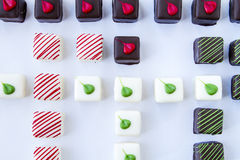 Assorted Petit Fours on White Background. Close up of assorted chocolate petit fours arranged in rows on white background Stock Photo
