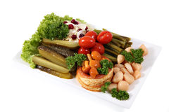 Assorted pickled vegetables on the plate, isolated over  white. Set on a plate of pickles, assorted pickles and pickled vegetables and mushrooms on a white Stock Images