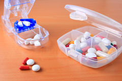Assorted pill box and pill cutter. Assorted pills and capsules in pill organizer and pill cutter Stock Photo