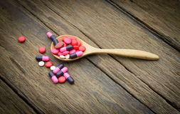 Assorted pills. And wood spoon on wood background royalty free stock image