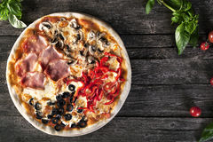 Assorted Pizza with bacon, mushrooms, peppers and olives on the Royalty Free Stock Photography