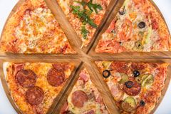 Assorted pizza with different fillings on a wooden platter. Assorted pizza with different fillings on wooden platter stock photo