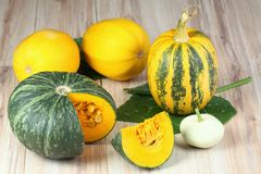 Assorted pumpkins and squashes on rustic wooden board Stock Photo