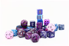 Assorted Purple Dice. An assortment of purple and blue dice in a variety of shapes and sizes photographed on a white background Royalty Free Stock Photos