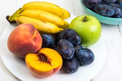 Assorted ripe fresh plums, bananas, peaches and apples on white table Royalty Free Stock Image