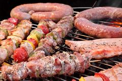 Assorted Roasted Meat with Vegetable On Barbecue Flaming Grill Stock Photo
