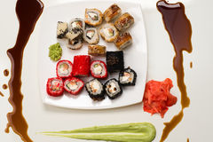 Assorted rolls, ginger, wasabi and soy sauce on white Royalty Free Stock Photos