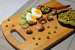 Assorted salad: canned green peas, pickled mushrooms, pickled cu. Cumbers on a black plate and boiled chicken eggs Stock Photography
