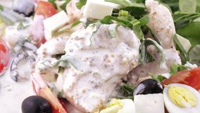 Assorted salad on lettuce leaves. Salad with chicken, olives, quail eggs, spinach, tomatoes, brynza, lemon, dressing with sour cream sauce and sprinkling with stock video