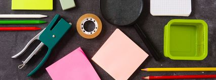 Assorted of school supplies on black slate. Back to school concept. Panorama view stock photography
