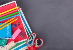 Assorted School Supplies on a Blackboard Background Royalty Free Stock Photo