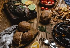 Assorted seafood and baked fish with bread and tomatoes Stock Photo