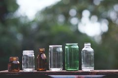 Assorted series collection of empty transparent glass bottle container in white, green and brown color, container reuse concept. Eco friendly concept royalty free stock image