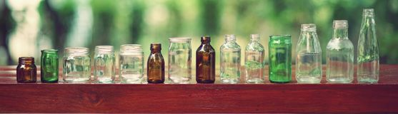 Assorted series collection of empty transparent glass bottle container in white, green and brown color, container reuse concept. Copy space stock image