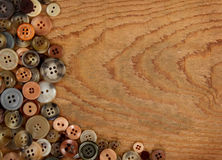 Assorted sewing buttons on a wooden background Stock Photos