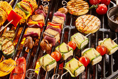 Assorted shish vegan kebabs with tofu and haloumi. Assorted shish vegan or vegetarian kebabs with tofu and haloumi grilling on a grill over barbecue with Royalty Free Stock Photography