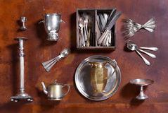 Assorted silver kitchenware arranged on wood. With cutlery, candlestick, ice bucket, egg cup, teapot tray and pitcher or jug viewed from above Royalty Free Stock Photo