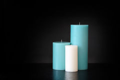 Assorted size candles, blue and white isolated on dark backgroun Royalty Free Stock Photos