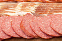 Assorted Slice Sausage and Bacon on Cutting Board Stock Image
