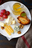 Assorted of sliced Cheese on white plate Royalty Free Stock Images