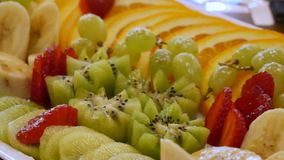 Dish of fresh fruit. Assorted sliced fruits on a plate. Sliced bananas, oranges, grapes, kiwi, strawberries close-up. delicious food on the table. A dish of stock footage