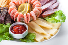 Assorted snacks: cheese, salami, shrimp, french fr Royalty Free Stock Images