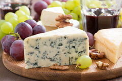 Assorted snacks and red wine, blue cheese, cheddar and camembert Royalty Free Stock Photography