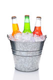 Assorted Soda Botles in Bucket. Three assorted soda bottles in a bucket filled with ice. Vertical Format over a white background with reflection stock image