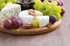 Assorted soft cheeses and fresh grapes on a wooden background Royalty Free Stock Images