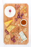 Assorted soft cheeses, grapes, nuts and honey on wooden board Stock Photo