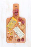 Assorted soft cheeses, grapes, nuts on a wooden cutting board Royalty Free Stock Photos