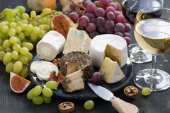 Assorted soft delicacy cheeses and snacks for wine on dark Royalty Free Stock Image