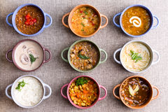 Assorted soups from worldwide cuisines. Displayed in bowls in three colorful lines garnished with cream and herbs in a World Of Soup concept, overhead view royalty free stock photos