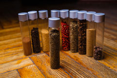 Assorted spices in bottles on wooden background Stock Photos