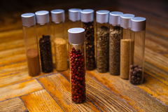 Assorted spices in bottles on wooden background Stock Image