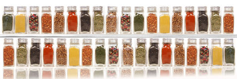 Assorted spices on two layer shelves against white royalty free stock photography