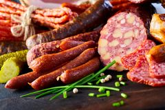 Assorted spicy seasoned sausages with fresh chives. Pickled cucumber or gherkin and peppercorns on a wooden table in a close up view Royalty Free Stock Images