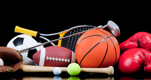Assorted sports equipment on black. Assorted sports equipment including a basketball, soccer ball, tennis ball, golf ball, bat tennis racket, boxing gloves Stock Image