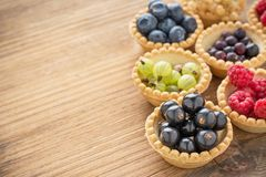 Assorted summer berries in tartlet of dough Royalty Free Stock Images