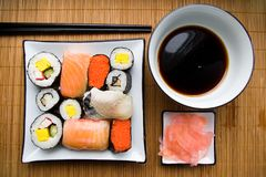 Assorted sushi on plate. Sushi settings: maki-suhi, unagi-sushi, sushi with caviar of flying fish, chops, plates, soya sauce, ginger royalty free stock photography