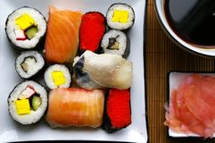 Assorted sushi on plate. Sushi settings: maki-suhi, unagi-sushi, sushi with caviar of flying fish, chops, plates, soya sauce, ginger royalty free stock photo